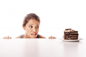 Studio shot of an attractive young woman being tempted by something sweet